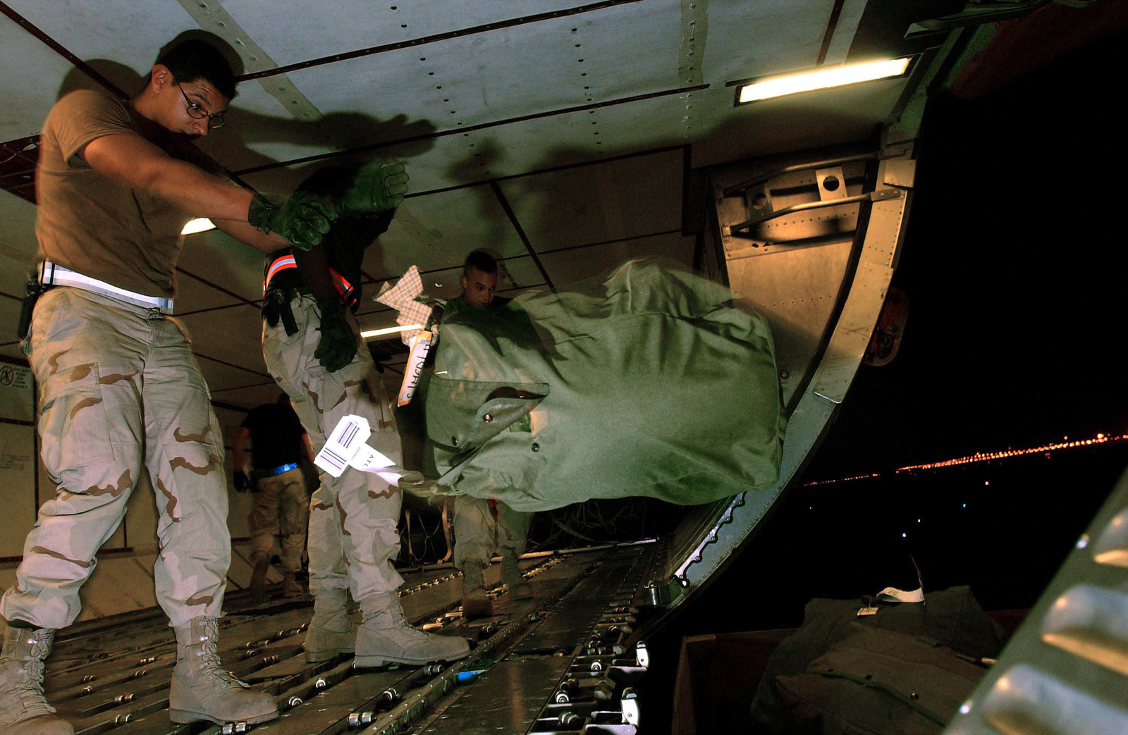 US Air Force (USAF) STAFF Sergeant (SSGT) Juan Hernandez, an Air Transportation Journeyman from the 320th Expeditionary Aerial Port Squadron (APS) downloads bags from a baggage rotator at a forward-deployed location, in support of Operation ENDURING FREEDOM