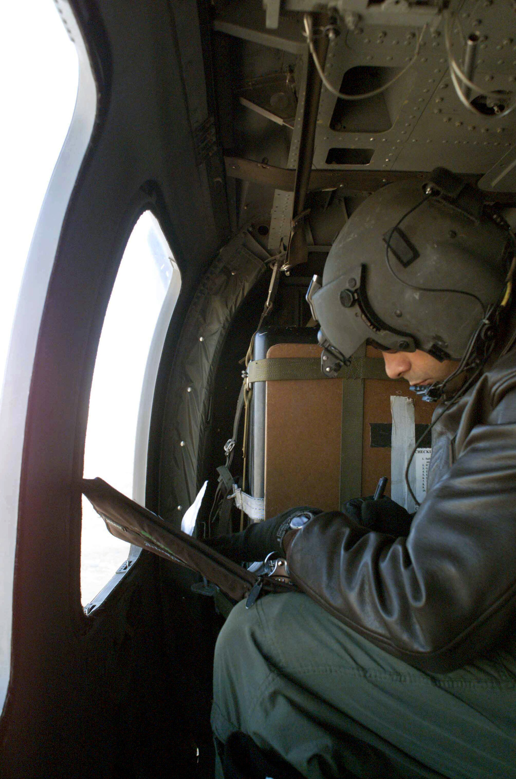 """US Air Force (USAF) Technical Sergeant (TSGT) Sal Flores, a Flight Engineer with the 305th Rescue Squadron (RS), makes an entry in his mission log while flying a mission in support of """"Santas in Blue."""""""