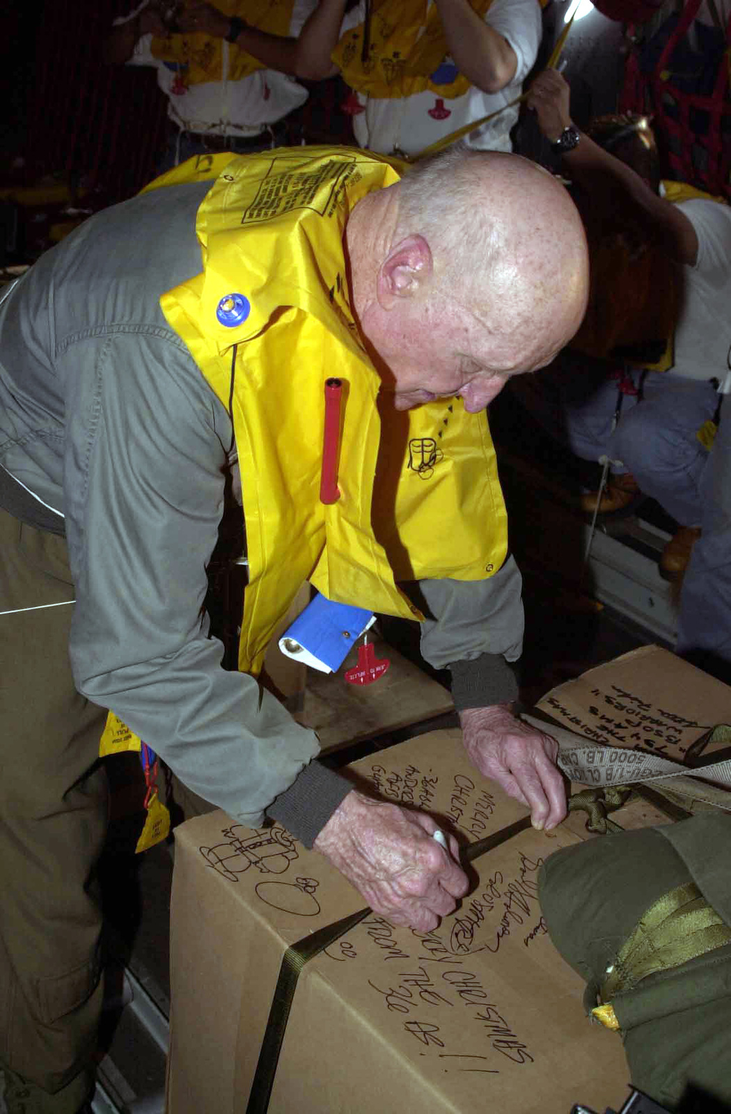 On board a US Air Force (USAF) C-130 Hercules from Yokota Air Base (AB), Japan, retired USAF Colonel (COL) Gail Halvorsen, the Candy Bomber, writes a holiday greeting on a box of supplies to be dropped during the first flight of the 50th anniversary flights called the Christmas Drop on Dec. 21 2002
