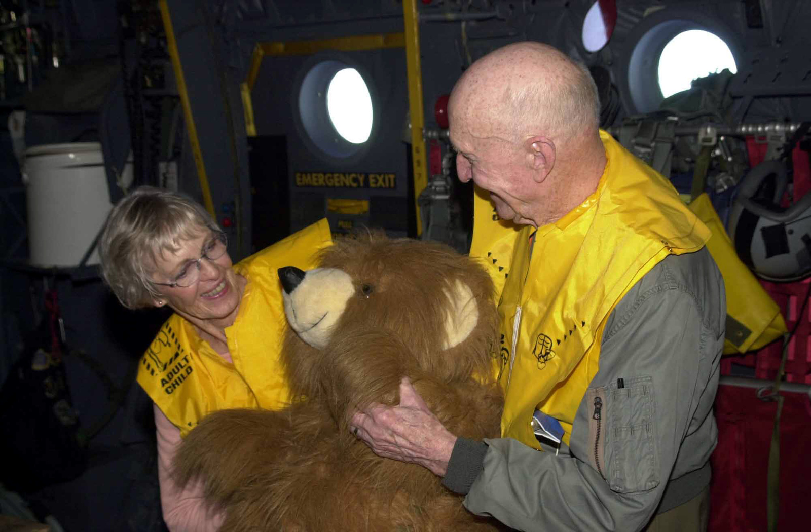 On board a US Air Force (USAF) C-130 Hercules from Yokota Air Base (AB), Japan, retired USAF Colonel (COL) Gail Halvorsen, the Candy Bomber and his wife Lorraine inspect a stuffed bear to be dropped during the first flight of the 50th anniversary flights called the Christmas Drop on Dec. 21 2002