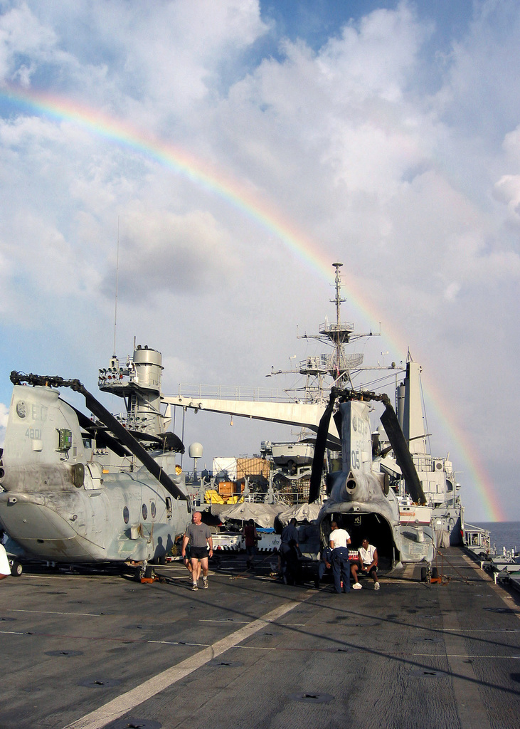 Marines and Sailors from the 24th Marine Expeditionary Unit (Special Operations Capable) (MEU SOC) aboard the USS AUSTIN (LPD 4), with the CH-46 Sea Knights on deck, catch a glimpse of a rainbow while heading to a liberty port after wrapping up a successful exercise in Kenya