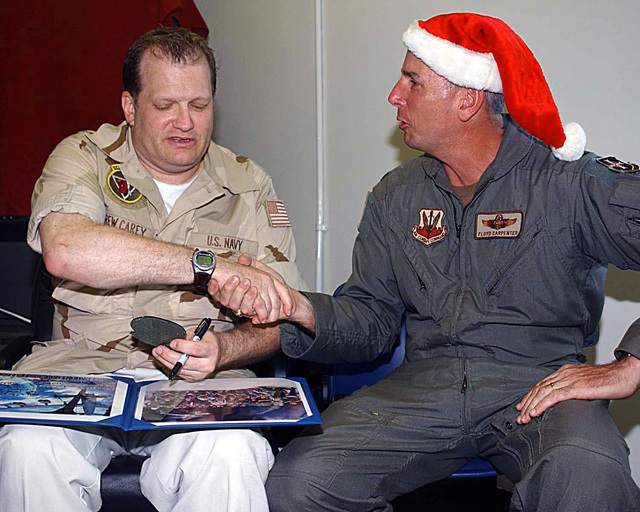 Christmas day, Comedian Drew Carey shakes hands with US Air Force (USAF) Colonel (COL) Floyd Carpenter, the 40th Air Expeditionary Wing (AEW) Commander, after receiving an organizational patch and photos of his visit to a forward-operating location during Operation ENDURING FREEDOM