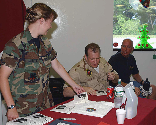 Christmas day, US Air Force (USAF) Second Lieutenant (2LT) Christine Millette, with the 40th Air Expeditionary Wing (AEW), Public Affairs Officer (PAO), helps Comedian Drew Carey as he signed autographs for personnel stationed at a forward-operating location in support of Operation ENDURING FREEDOM