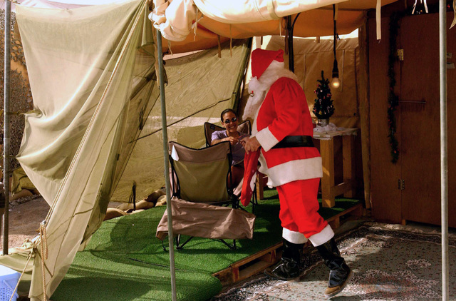 US Air Force (USAF) STAFF Sergeant (SSGT) Rob Theiler, a liquid fuels craftsman deployed to the 320th Expeditionary Civil Engineering Squadron (CES), dressed as Santa Clause, passes out candy canes to bring a Christmas spirit to the tent city at a forward-deployed location in support of Operation ENDURING FREEDOM