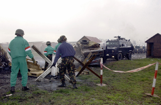 Members of the Italian Multinational Specialized Unit (MSU) playing the role of angry protesters build a barrier after MSU armored vehicles tore down the barrier, during a mock civil disturbance demonstration exercise on Camp Butmir at Sarajevo, Bosnia and Herzegovina, in support of Operation JOINT FORGE