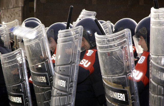 Members of the Italian Multinational Specialized Unit (MSU) prepare to disperse fellow MSU members playing the role of an angry mob of protesters during a mock civil disturbance demonstration exercise on Camp Butmir at Sarajevo, Bosnia and Herzegovina, in support of Operation JOINT FORGE