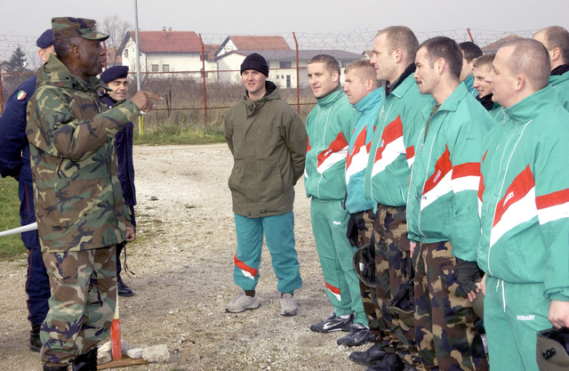 US Army (USA) Lieutenant General (LGEN) William E. Ward, Commander of Stabilization Force (COMSFOR), talks with members of the Multinational Specialized Unit (MSU) Italian Carabinieri which played the role of angry protesters during a mock civil disturbance demonstration on Camp Butmir at Sarajevo, Bosnia and Herzegovina, in support of Operation JOINT FORGE
