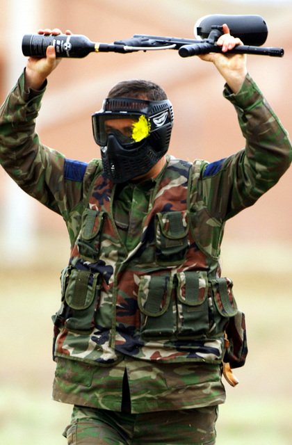 A Turkish Air Force Sergeant (SGT) surrenders, raising his Tippmann Custom 98 RT paintball gun, after taking a direct hit to his face mask during the American and Turkish security forces training. They are practicing combat tactics, fire-control measures, cover and concealment procedures, using paintball gear at Incirlik Air Base (AB), Turkey. The use of Paintball gear in their training and curriculum once a quarter emphasizes the importance of fire-control measures along with cover and concealment procedures