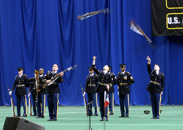 "The US Army (USA) Drill Team performs in the ""Twilight Tattoo"" by tossing rifles into the air in a synchronized drill, at the Alamodome in San Antonio, Texas"