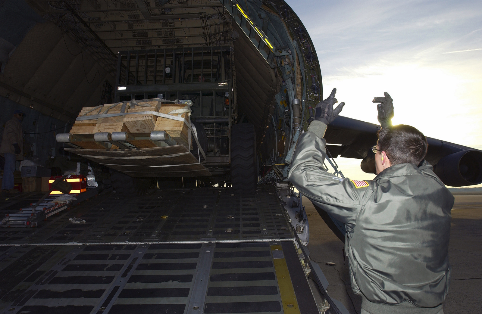US Air Force (USAF) STAFF Sergeant (SSGT) Josh Myer (right), Loadmaster, 22nd Airlift Squadron (AS), Travis Air Force Base (AFB), California (CA), marshals a John Deere 544E 10K forklift with cargo onboard the C-5 Galaxy. The C-5 and its load are deploying in support of Operation ENDURING FREEDOM