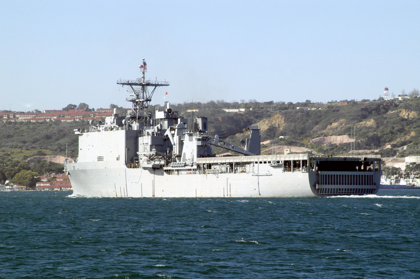 Quarter port stern view of the US Navy (USN) WHIDBEY ISLAND CLASS; DOCK LANDING SHIP, USS RUSHMORE (LSD 47), underway in the Harbor at San Diego, California (CA), as the ship departs for a scheduled six-month deployment
