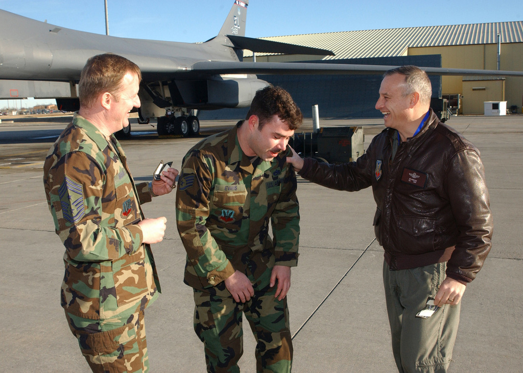"""US Air Force (USAF) STAFF Sergeant (SSGT) Anthony Evans, 28th Aircraft Maintenance Squadron (AMS), gets a big surprise on the flightline when USAF Colonel (COL) James M. Kowalski, Commander, 28th Bomb Wing (BW), and USAF Command CHIEF MASTER Sergeant (CCMSGT) Donald Ingram, 28th BW, award him a promotion to USAF Technical Sergeant (TSGT) under the Stripes for Exceptional Performers program. Newly promoted TSGT Evans thought he was present to participate in an MSNBC interview with COL Kowalski, when he was informed he was out of uniform and his new rank """"tacked"""" on"""