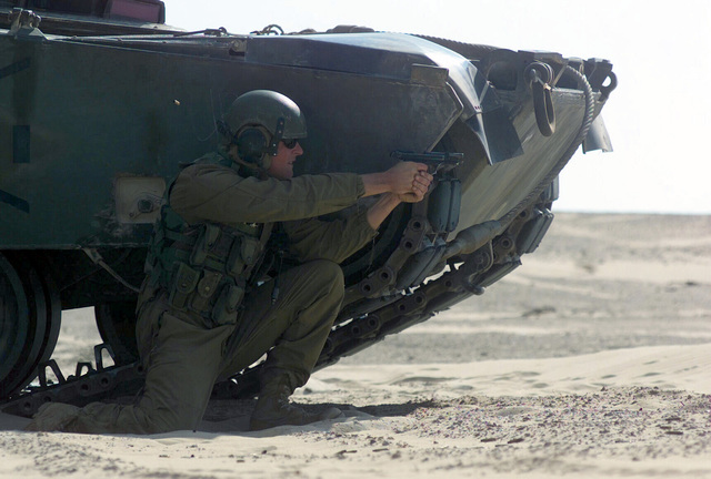 US Marine Corps (USMC) Corporal (CPL) Ross D. Raper, a M1A1 Abrams Main Battle Tank (MBT) gunner, assigned to Battalion Landing Team, 2nd Battalion, 2nd Marines, 24th Marine Expeditionary Unit (MEU) Special Operations Capable (SOC), practices engaging targets, with his M9 9mm service pistol, on a live fire range in Central Command's Area of Responsibility during Operation ENDURING FREEDOM