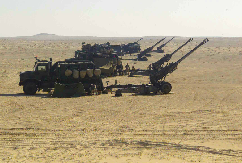 Six US Marine Corps (USMC) M198 155mm Towed Howitzers, assigned to Fox/Battery, Battalion Landing Team (BLT), 2nd Battalion, 2nd Marines, 24th Marine Expeditionary Unit (MEU), Special Operations Capable (SOC), sit configured in a firing position with their MK-23 Medium Tactical Vehicle Replacement (MTRV), 7-ton cargo trucks, during a training exercise conducted in the US Central Commands (USCENTCOM) Area of Responsibility (AOR), to support Operation ENDURING FREEDOM