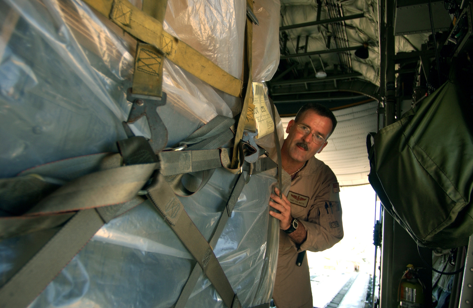US Air Force (USAF) Technical Sergeant (TSGT) Tim Watts, a loadmaster from the Oklahoma City Air National Guard (ANG), loads cargo pallets onto a C-130 Hercules cargo aircraft in support of Operation ENDURING FREEDOM