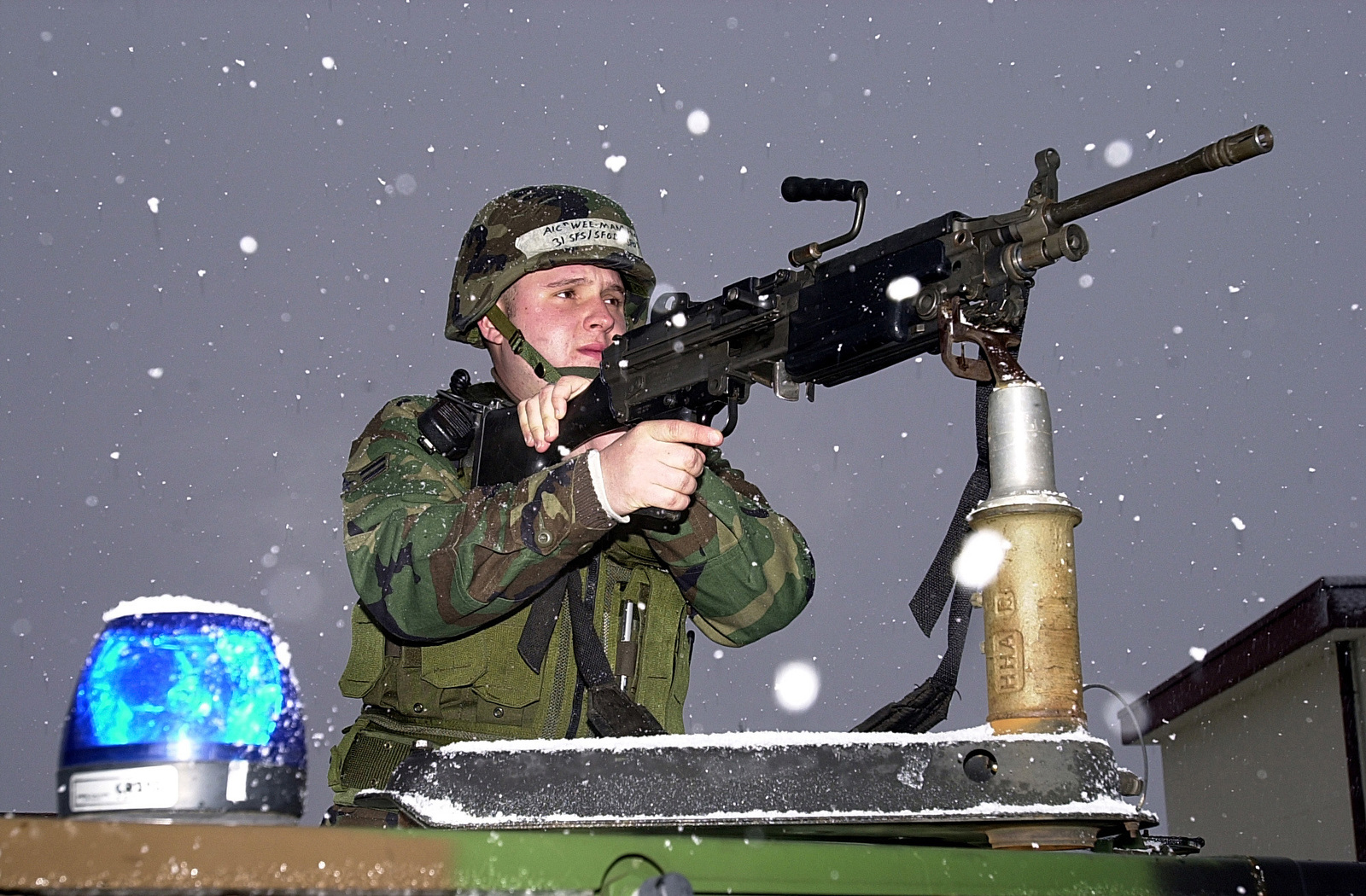 As the first major snowfall of the season covers Aviano Air Base (AB) in white, US Air Force (USAF) AIRMAN First Class (A1C) Brian Hirsch, 31st Security Forces Squadron (SFS) maintains security cover with a FNMI 5.56 mm M249 Squad Automatic Weapon (SAW) at Aviano's main gate