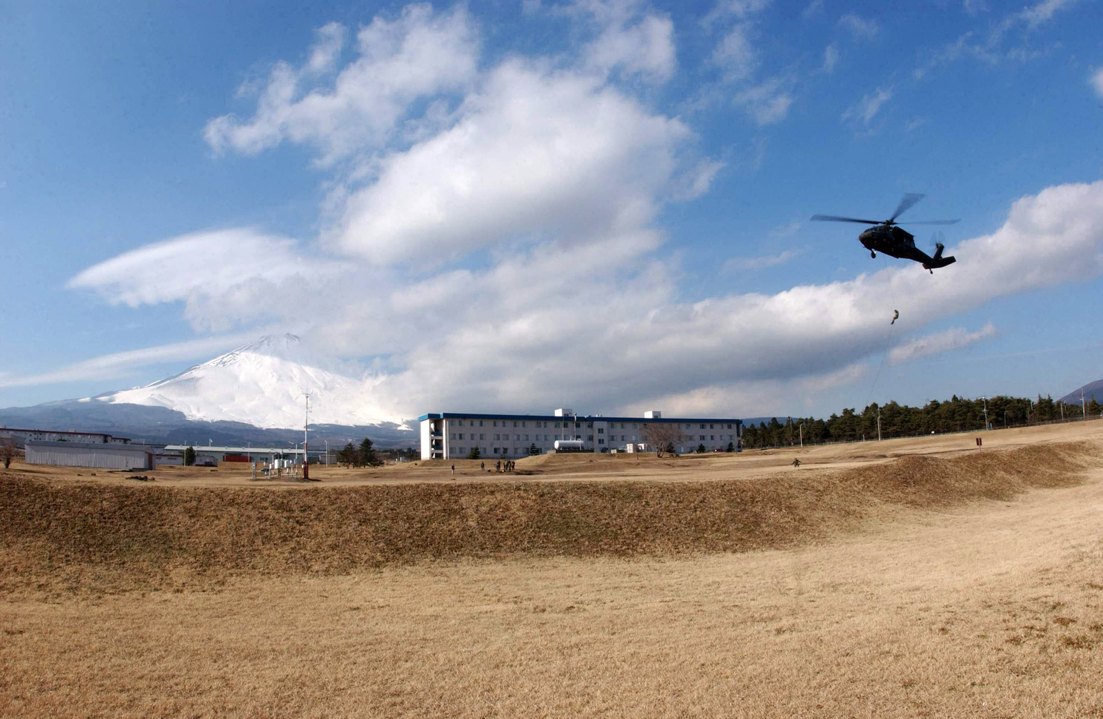 With Mt. Fuji as a backdrop, US Air Force (USAF) and US Marine Corps (USMC) members rappel from a US Army (USA) UH-60 Black Hawk helicopter from the 78th Aviation Battalion, Camp Zama, Japan, at Camp Fuji, Japan