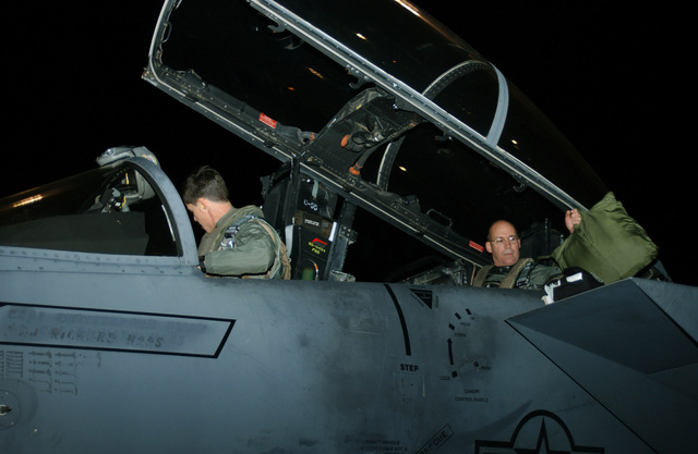 US Air Force (USAF) Major (MAJ) Mike Morrison (right), Weapons System Officer (WSO), 336th Fighter Squadron (FS), Seymour Johnson Air Force Base (AFB), North Carolina (NC), pulls his flight bag inside a USAF F-15E Strike Eagle before he takes-off on deployment in support of operations at forward locations. The 336th is one of two Fighter Squadrons at Seymour that operates on a 120-day rotational on-call status