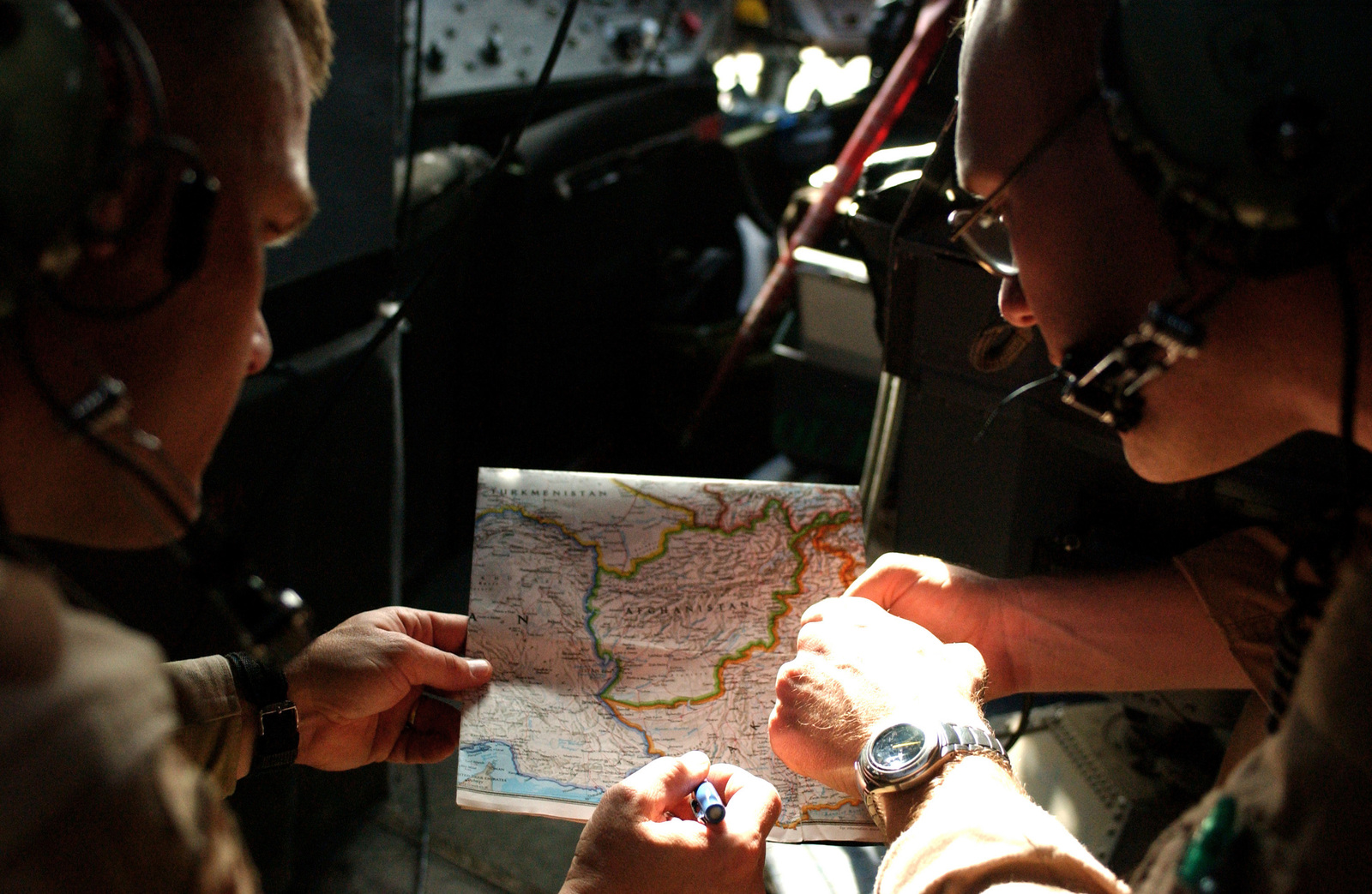 US Army (USA) Colonel (COL) Bob Derrick, USA Corps of Engineers (USACE), Transatlantic Program Center and US Air Force (USAF) First Lieutenant (1LT) Brian Knudson, a C-130 Hercules navigator with the 772nd Expeditionary Airlift Squadron (EAS), study a map of Southwest Asia at a forward-deployed location, prior to flying a mission in support of Operation ENDURING FREEDOM