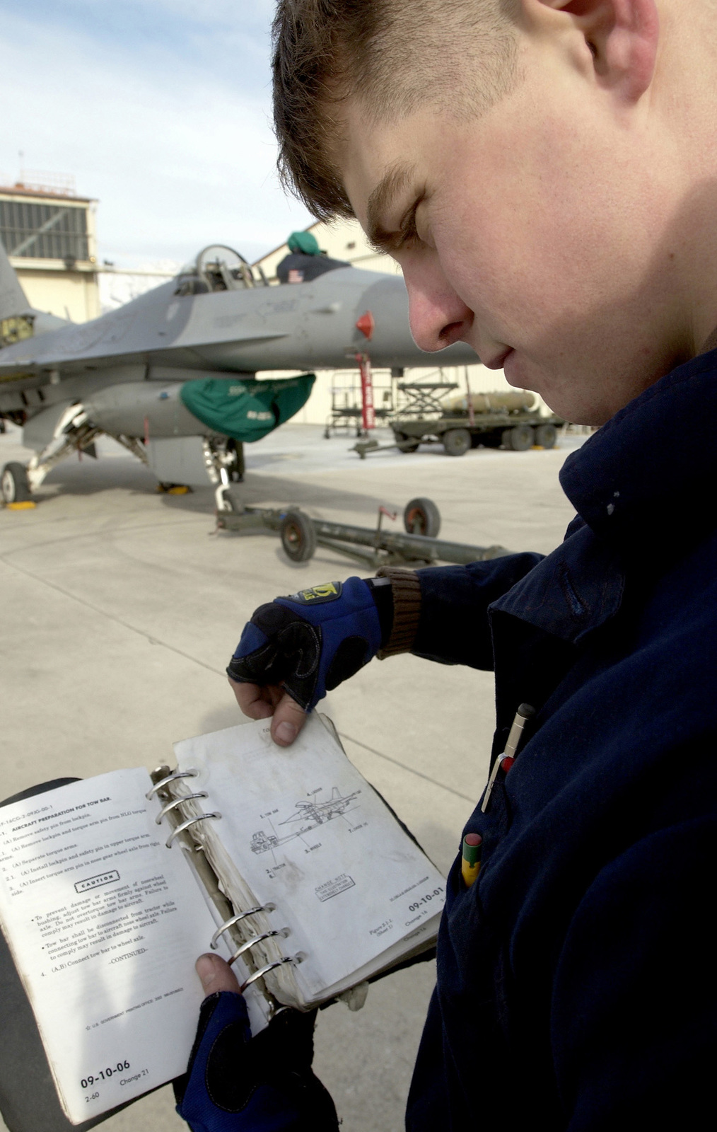 US Air Force (USAF) SENIOR AIRMAN (SRA) Colin George, Crewchief, 31st Maintenance Squadron (MXS), Aviano Air Base (AB), Italy reviews the Technical Order (TO) before members of the F-16 phase team move the aircraft into the hangar to continue the 300-hour phase inspection