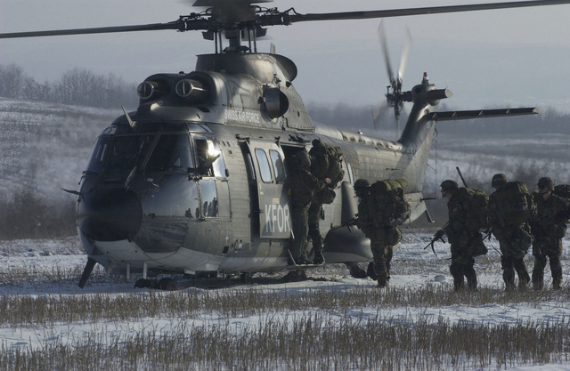 Soldiers move board a Swiss Air Force AS-332 Super Puma helicopter on the Heritage Drop Zone near Klina, Kosovo, after an airborne assault, in support of Operation JOINT GUARDIAN II