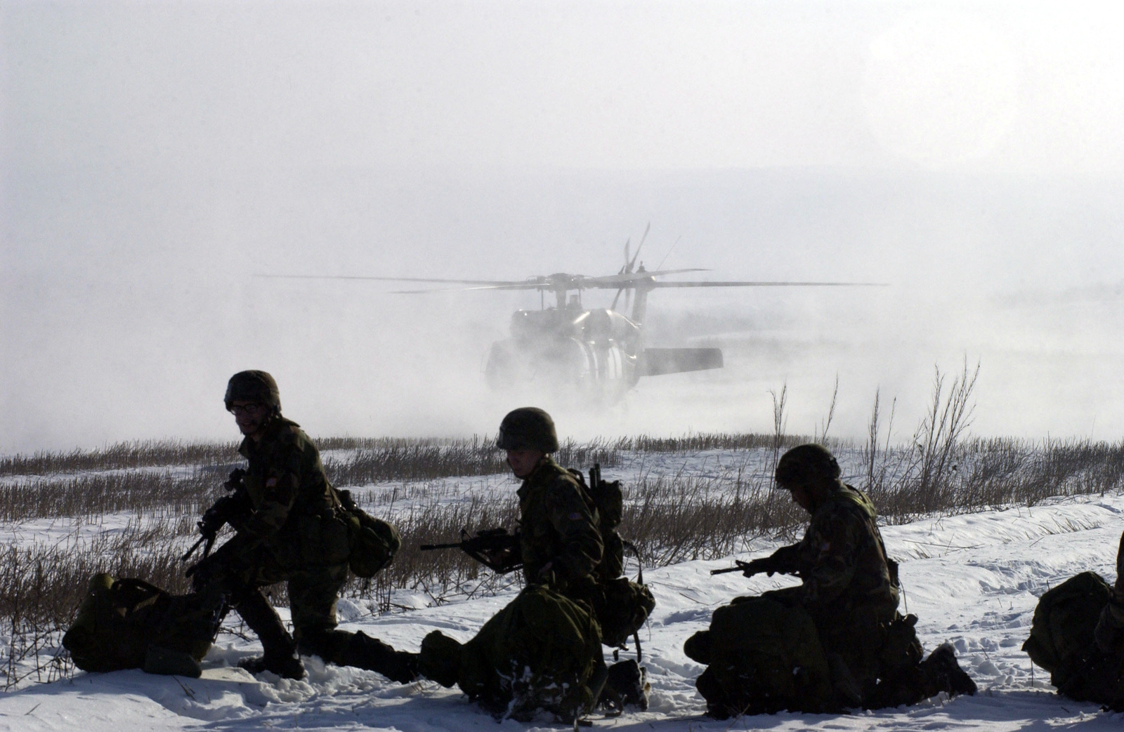 Soldiers wait on the snow covered ground before boarding UH