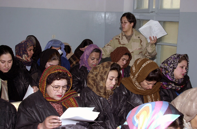 US Army (USA) Sergeant (SGT) Bonnie Collins with the 126th Finance Detachment, Fort Polk, Louisiana, passes out her English lesson plan during English class for Afghan women at the Rabia Balkhi Hospital in Kabul, during Operation ENDURING FREEDOM
