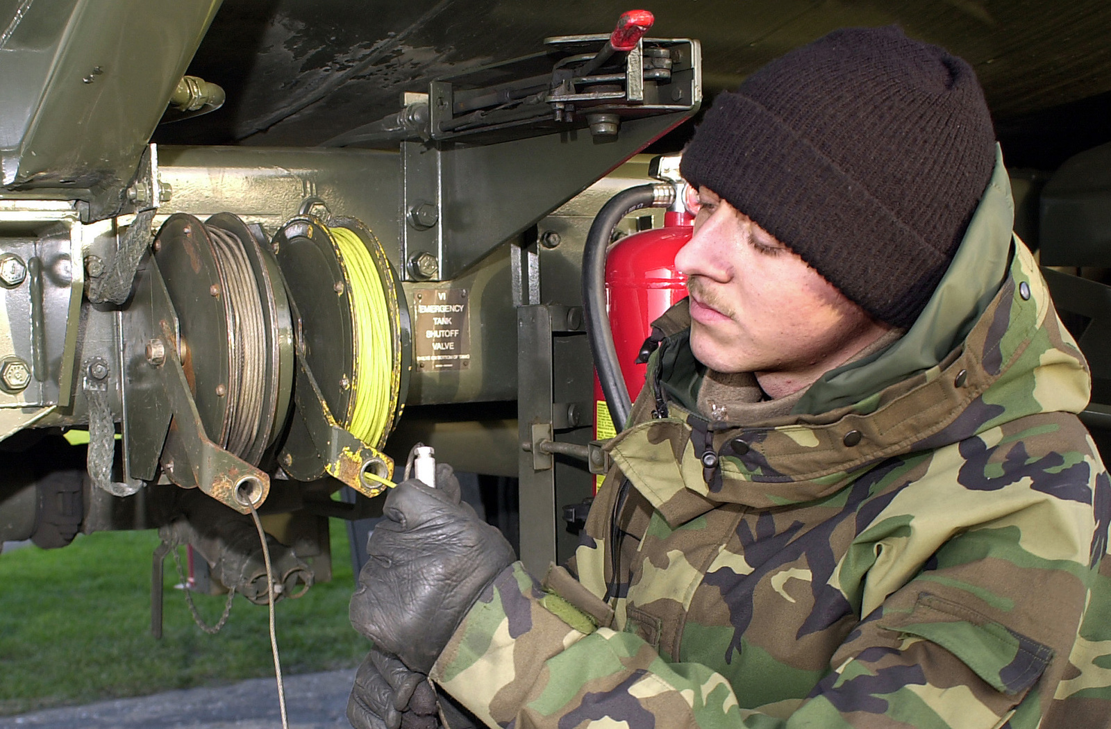 US Air Force (USAF) AIRMAN First Class (A1C) Christopher Meredith, 100th Logistics Readiness Squadron (LRS), inspects a bonding plug and cable on his fuel truck at RAF Mildenhall, United Kingdom. The inspection is part of a daily routine to ensure all fuel trucks meet safety requirements and are fully operational