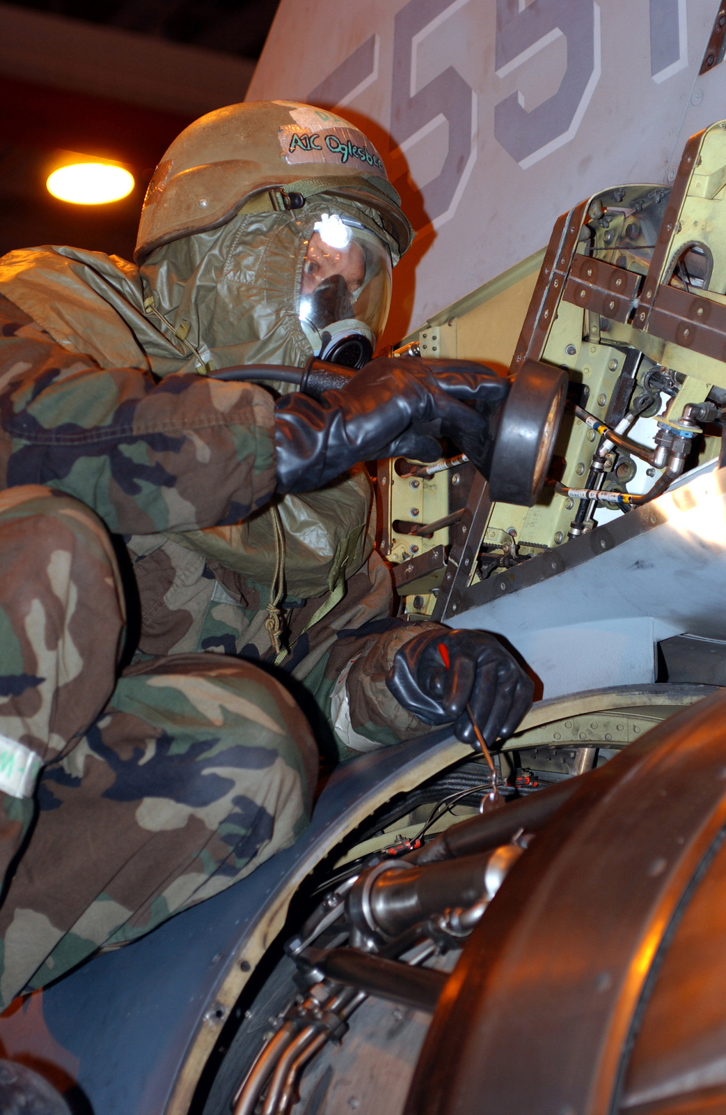 US Air Force (USAF) AIRMAN First Class (A1C) Jared Oglesbee, Crewchief, 31st Aircraft Maintenance Squadron (AMXS), performs routine maintenance, while in Mission-Oriented Protective Posture response level 4 (MOPP-4), on an F-16 Fighting Falcon during the LOCAL SALTY NATION exercise. The LSN prepares members of the 31st Fighter Wing (FW) for an upcoming Tactical Evaluation