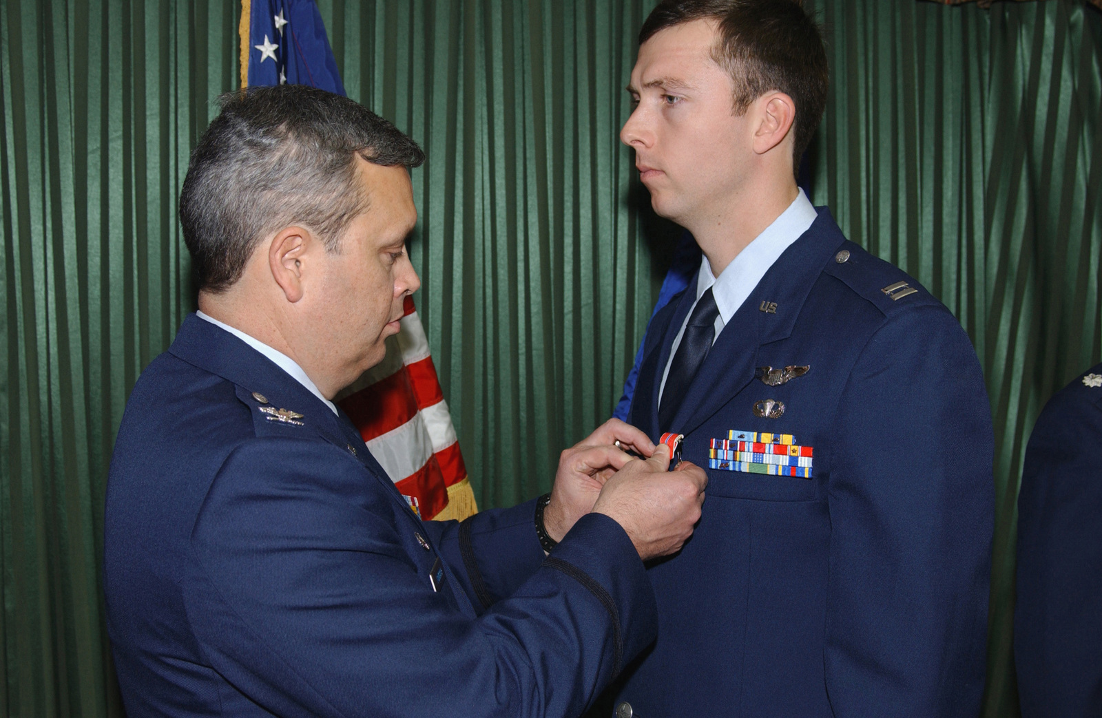 US Air Force (USAF) Colonel (COL) Michael A Longoria (left), Commander, 18th Air Support Operations Group (ASOG), Pope Air Force Base (AFB), North Carolina (NC), pins the Bronze Star on USAF Captain (CAPT) Timothy B Piccin, 17th Air Support Operations Squadron (ASOS), Hunter Army Airfield (AAF), Georgia (GA). They awards ceremony was held at the Hunter Club on the base