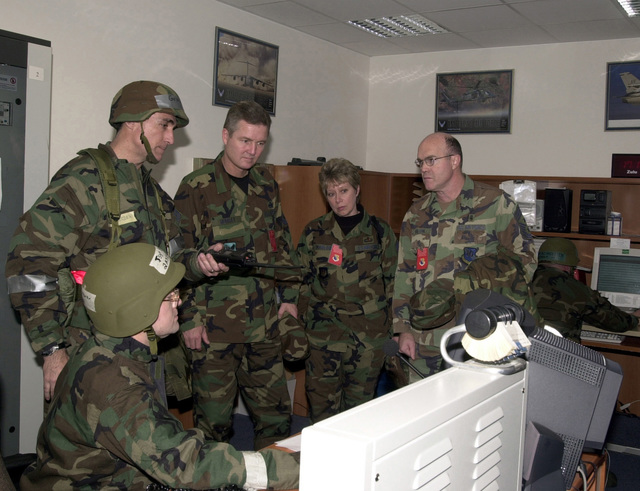 US Air Force (USAF) Technical Sergeant (TSGT) Paul Brewer (left, seated), 31st Maintenance Operations Squadron (MOS), shows the aircraft readiness board to USAF CHIEF MASTER Sergeant of the Air Force (CMSAF) Gerald R. Murray (center), as USAF Brigadier General (BGEN) R. Mike Worden (left with helmet), Commander, 31st Fighter Wing (FW), points out how the board keeps 31st FW Battle STAFF updated with sortie information during the LOCAL SALTY NATION exercise. CMSAF Murray will receive an orientation briefing about Air Force members and the mission of Aviano AB and discuss issues important to enlisted personnel