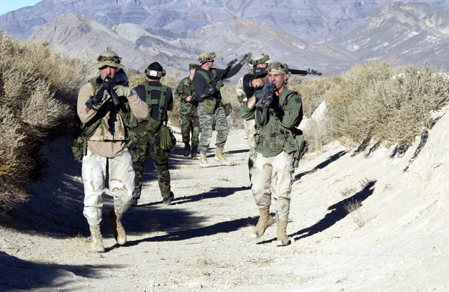 Instructors at the Air base Defense School, 99th Ground Combat Training Squadron (GCTS), Indian Springs Air Force Auxiliary Air Field (AAF), Nevada (NV), pose as a hostile force attempting to breach the defenses of a simulated forward deployed air base. The instructors wear Multiple Integrated Laser Engagement System (MILES) it detects if they are shot by the defenders. They are also armed with 5.56 M16A2 assault rifles with MILES attachments. The 99th GCTS trains all of Air Combat Commands Security Forces on base defense in a hostile environment, and is the oldest school on ground air base defense tactics in existence
