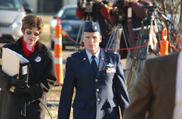 US Air Force (USAF) Major (MAJ) William Umbach, and his wife Marlene, enroute to the Article 32 hearing room at Barksdale Air Force Base (AFB), Louisiana (LA). USAF Major Umbach is one of two pilots involved in the Tarnak Farms Friendly Fire incident on April 17, 2002 that killed four Canadian soldiers and injured eight near Kandahar, Afghanistan. The Article 32 hearing investigation of the charges against the two pilots determines whether to try by court-martial. In the background are some of the many media members covering the hearing