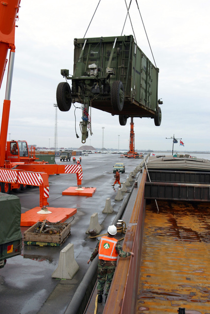 US Army (USA) Sergeant First Class (SFC) Lewis R. Cass, 840th Transportation Battalion, Headquarters 598th Transportation Group, Military Traffic Management Command, watches as a ESCO Datron Container Load Trailer (CLT) and Dolly Set is off-loaded from a barge, at the port in Antwerp, Belgium