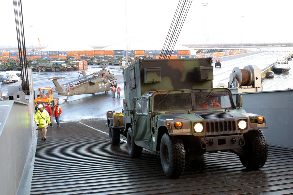 A US Army (USA) High-Mobility Multipurpose Wheeled Vehicle (HMMWV) equipped with a compatible shelter is driven aboard the US Navy (USN), Military Sealift Command (MSC). WATSON CLASS: Large, Medium-Speed Roll-on/Roll-off Ship (LMSR), USNS WATKINS (T-AKR-315), as aircraft, equipment, and supplies from the USA 22nd Signal Battalion, 7th Signal Brigade, 5th Signal Command, is loaded for shipment, on the pier at Antwerp, Belgium