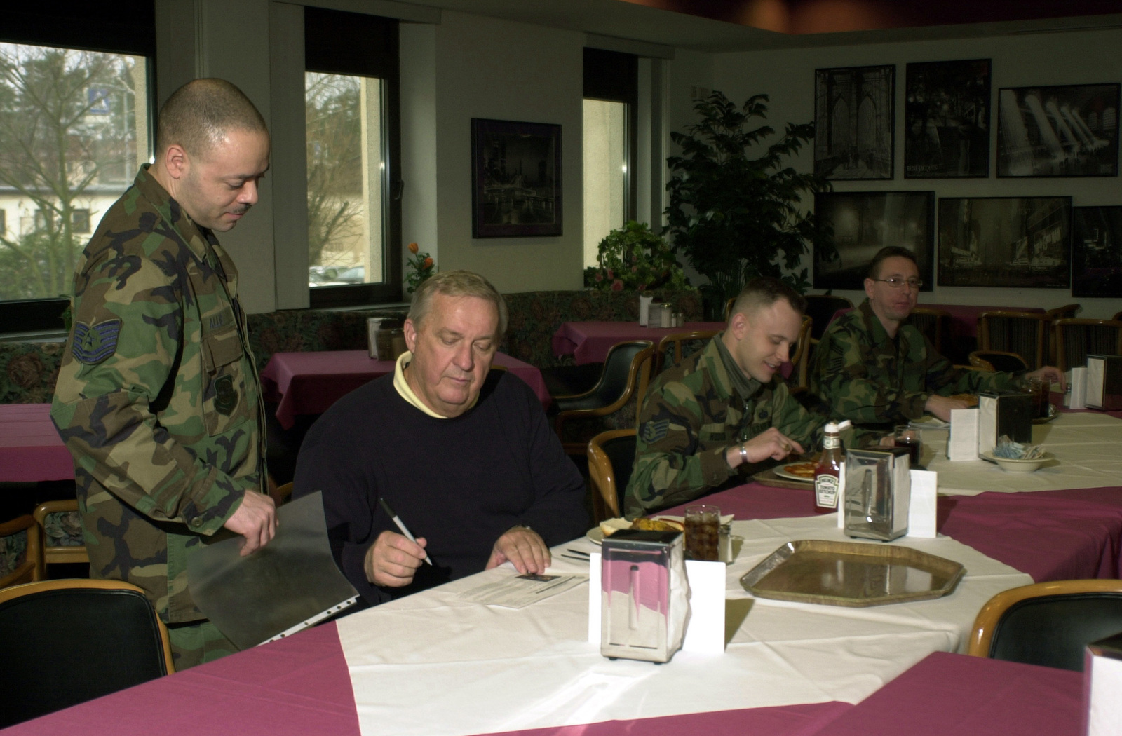 US Air Force (USAF) CHIEF MASTER Sergeant of the Air Force (CMSAF) (ret) James C. Binnicker signs his biography sheet for USAF Technical Sergeant Zamounde Allie, 723rd Air Mobility Squadron (AMS), during the chief's visit to the Rheinland Inn Dining Facility at Ramstein Air Base (AB), Germany