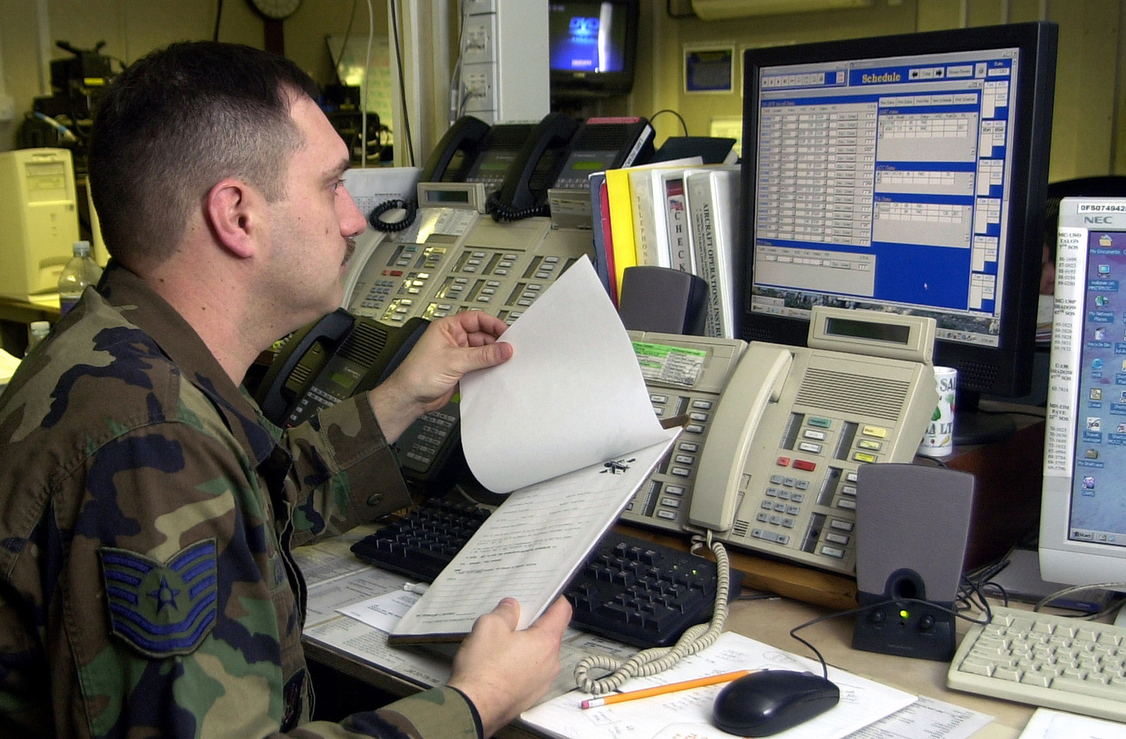 US Air Force (USAF) Technical Sergeant (TSGT) John Cormiea, Maintenance Operations Center SENIOR Controller, 100th Maintenance Operations Squadron (MOS), reviews the prior permission request log to ensure an inbound aircraft has permission to land at RAF Mildenhall