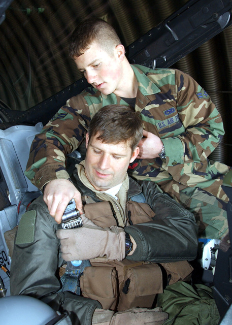 """US Air Force (USAF) AIRMAN First Class (A1C) Scott Ebert, a Crew CHIEF assigned to the 55th Expeditionary Fighter Squadron (EFS), lends assistance to a unidentified USAF F-16CJ Fighting Falcon aircraft Pilot, with the call sign of """"Buzz,"""" with his safety harness, inside the cockpit of his aircraft prior to a mission at Incirlik Air Base (AB), Turkey, during Operation NORTHERN WATCH"""