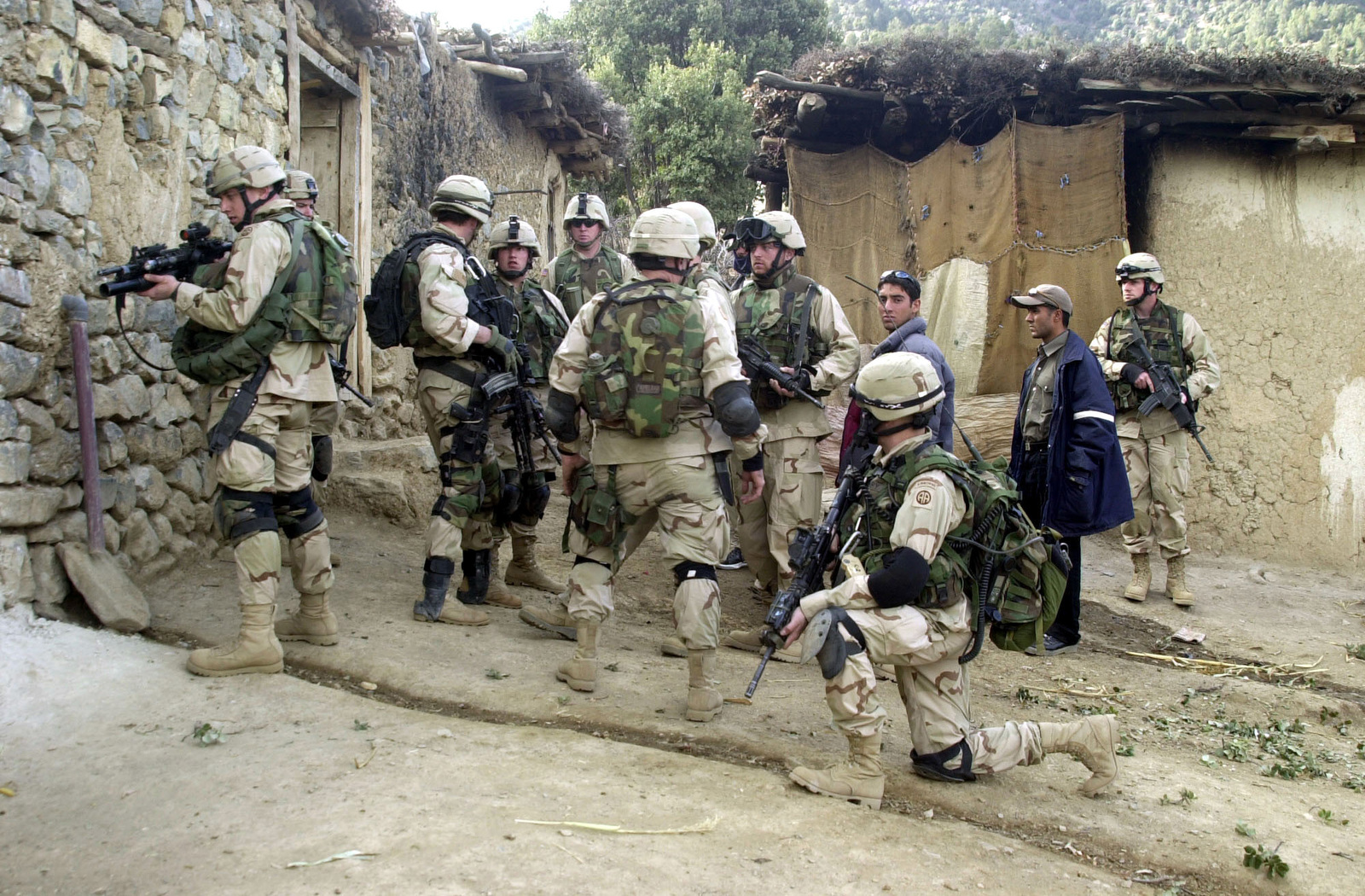 """Soldiers of """"C"""" Company, 1ST Battalion, 504th Parachute Infantry Regiment (PIR), armed with 5.56mm M4 Carbines and equipped with interceptor body armor, knee pads, use tactical satellite telephones, while conducting a search for suspected Taliban in the city of Naray, in support of ENDURING FREEDOM"""