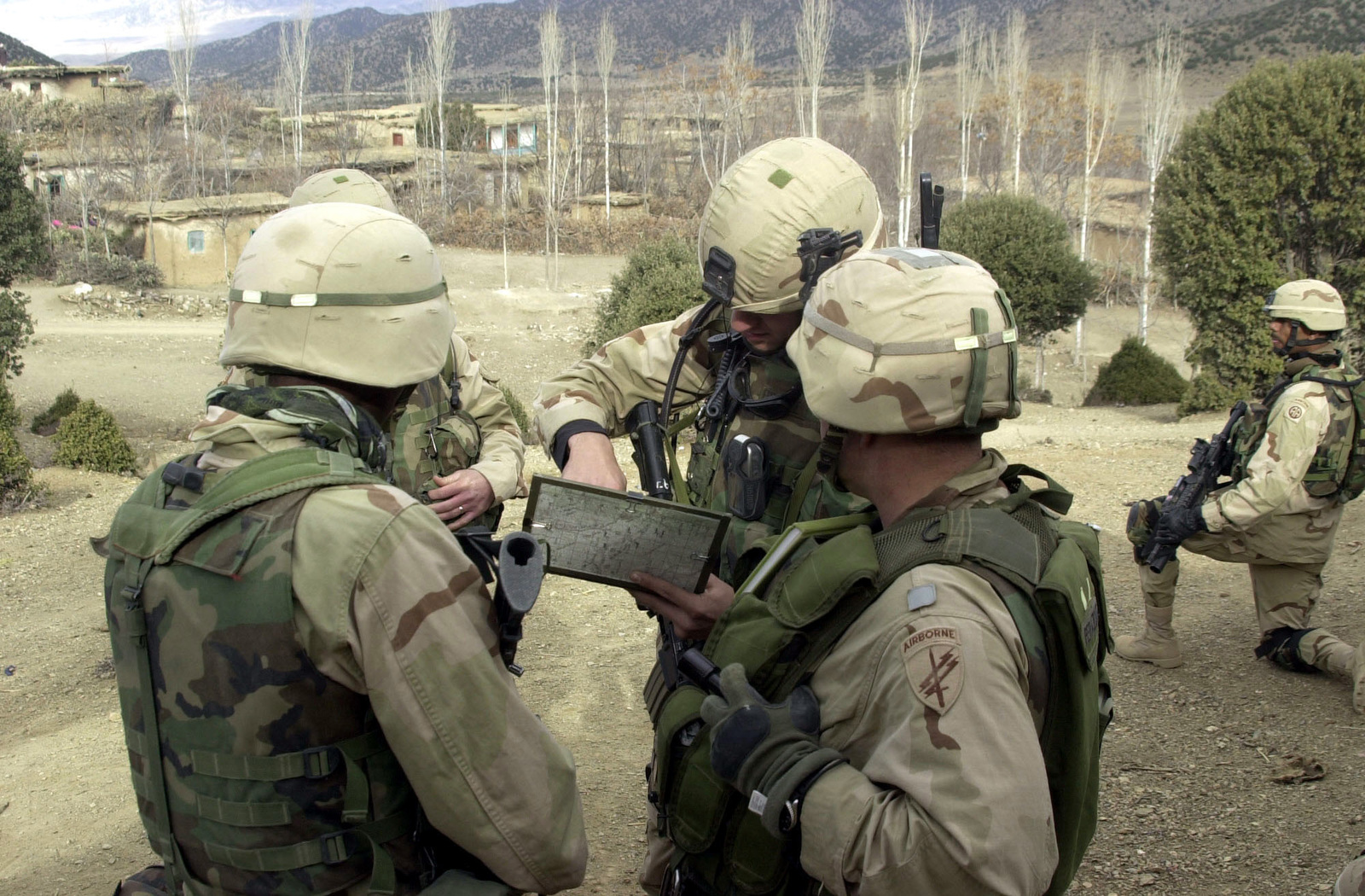 """Special Forces Group (SFG) soldiers of """"C"""" Company, 1ST Battalion, 504th Parachute Infantry Regiment (PIR), armed with 5.56mm M4 Carbines and equipped with interceptor body armor, knee pads, use tactical satellite telephones, while conducting a search for suspected Taliban in the city of Naray, in support of ENDURING FREEDOM"""