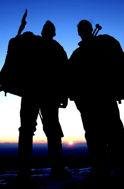 US Air Force (USAF) Captain (CAPT) Damian Schlussel (left), Officer in Charge (OIC) Security Forces Training Flight, 31st Security Forces Squadron (SFS) and USAF SENIOR AIRMAN (SRA) Chris Hucks, Communications Project Manager, 31st Communications Squadron (CS), pause to observe the sunrise from Mount Cavallo near Aviano, Italy. They are out fitted with mountaineering gear for a day of climbing and repelling training