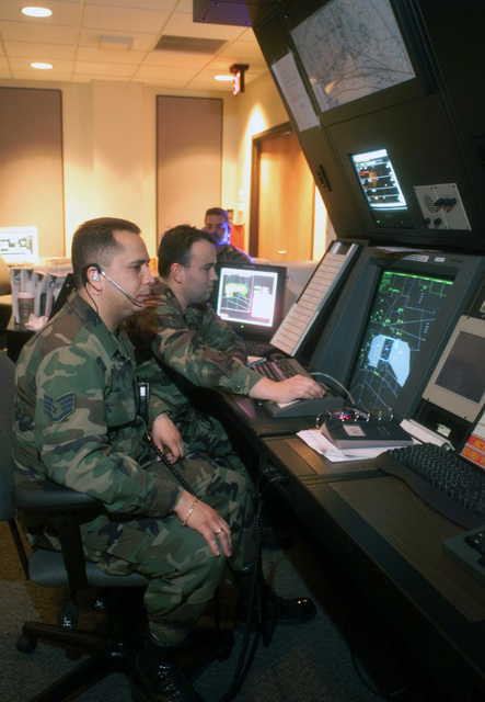 US Air Force (USAF) STAFF Sergeant (SSGT) Ruben Muniz (front) and USAF SSGT Jeremy Toche concentrate on the Air Traffic Control Screen RAPCON (Radar Approach Control) at the Eglin Air Force Base (AFB), Florida (FL), while USAF Technical Sergeant (TSGT) Bud Thacker, Watch Supervisor, looks on in the background