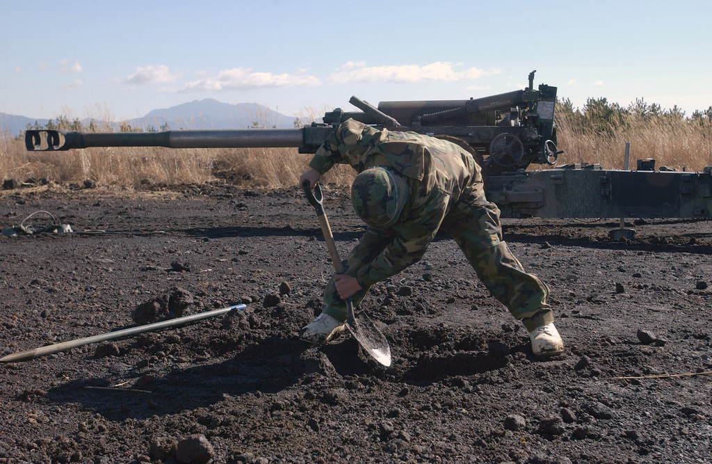 At Camp Fuji, Japan (JPN), an M198 155 mm Medium Towed Howitzer sits ready while a US Marine Corps (USMC) Cannonneer Lance Corporal (LCPL) Jorge Cruz, with Sierra Battery, 5th Battalion, 10th Marine Regiment, digs a small fighting hole that he will later use during an air raid drill