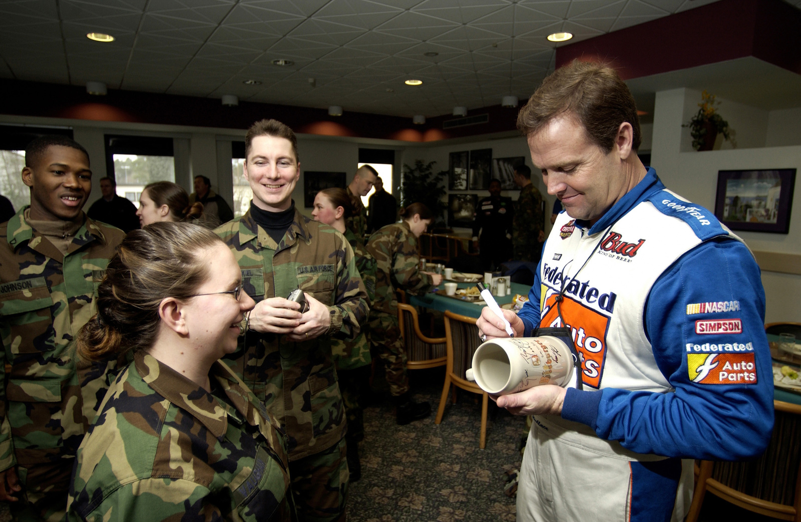 National Association for Stock Car Auto Racing (NASCAR) Mike Wallace, driver for Team Freedom Racing, signs autographs for Air Force and Army service members during a luncheon at Ramstein Air Base (AB), Germany. NASCAR celebrities are touring Europe as part of a joint venture with the Department of Defense and the Employers Support of Guard and Reserve to boost morale and show employers back home what Guard troops are accomplishing