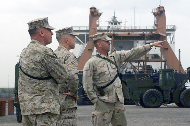 US Marine Corps (USMC) Captain (CAPT) Kevin Rosen provides Major General (MGEN) James Amos and Brigadier General (BGEN) Terry Robling with a tour of the staging area for the maritime pre-positioning ship off load sight near Shuaiba Port, Kuwait, in support of Operation ENDURING FREEDOM