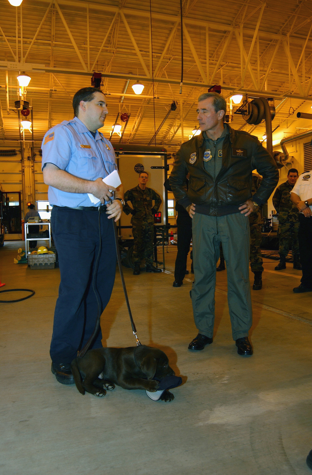 Mr. David Killpack (left), a Firefighter with the 92nd Civil Engineer Squadron (CES), and US Air Force (USAF) Major General (MGEN) John D. Becker, Commander, 15th Air Force, discuss the training his 11-week old black Labrador retriever Toby, will need to become a Disaster Response K-9