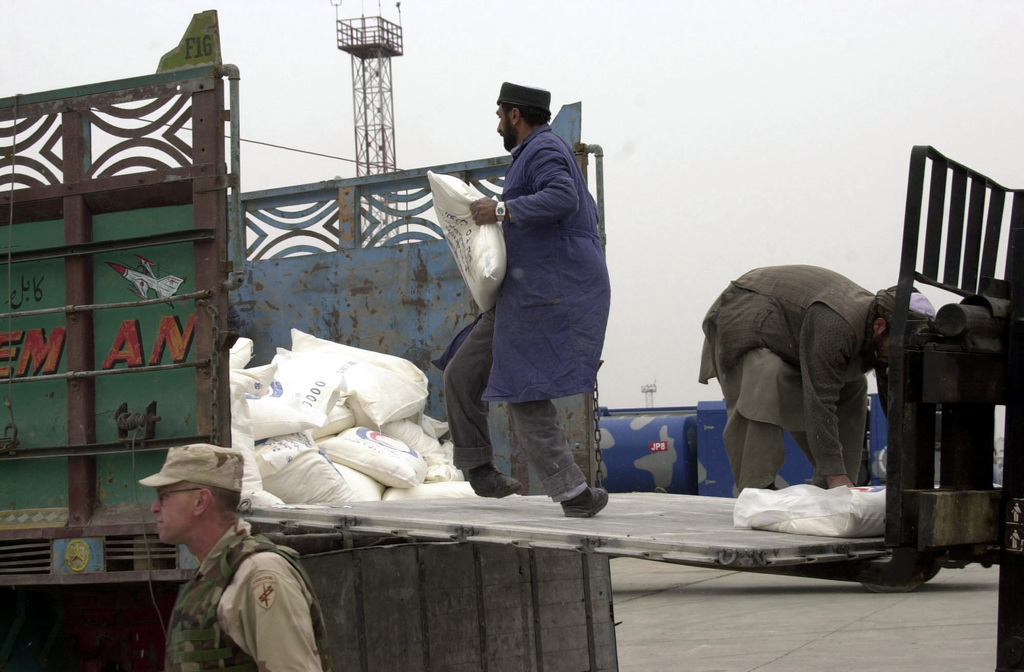 Two Afghans men load bags of flour from a forklift, onto the back of an open truck at Kabul International Airport, in support of ENDURING FREEDOM