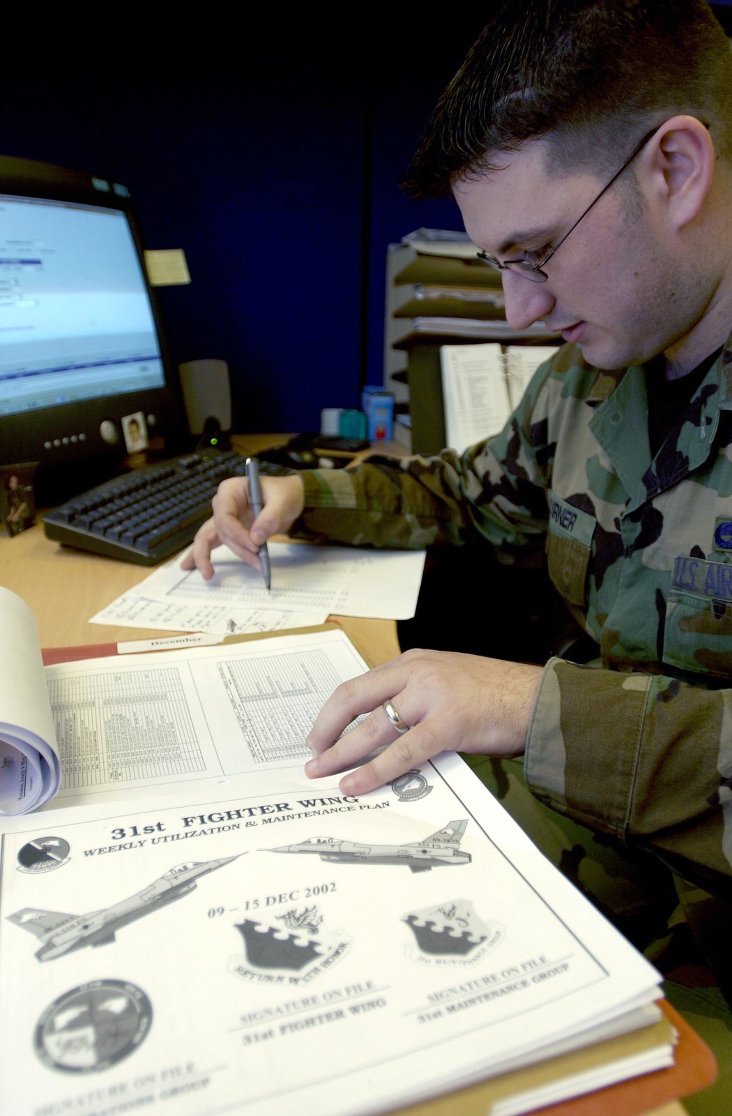 US Air Force (USAF) SENIOR AIRMAN (SRA) Billy Turner, Deficiency Liaison Analyst, 31st Maintenance Operations Squadron (MOS), Aviano Air Base (AB), Italy, pours over collected information about aircraft maintenance. He will supply this information to Maintenance Analysts who will project the Wings status