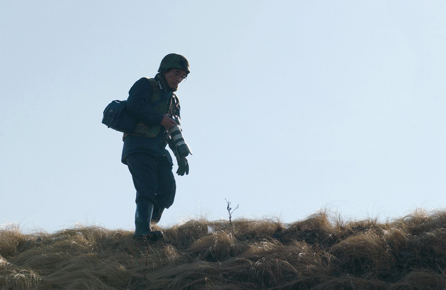 A Japanese press photographer walks on a hill looking for his next shot. During Media Day the Japanese press are hosted by the US Marine Corps (USMC) 3rd Battalion, 12th Marine Regiment and given a demonstration on the operational cycle of fire that takes place during an artillery relocation exercise at the East Fuji Maneuver Area (FMA), Japan (JPN)