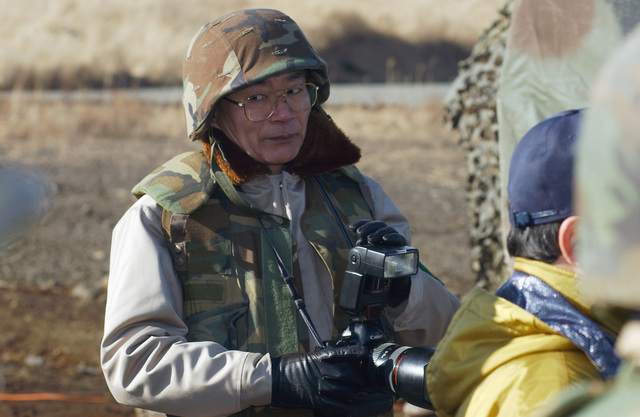 During Media Day a member of the Japanese press wears protective gear and listens as personnel with the 3rd Battalion, 12th Marine Regiment, demonstrate the operational cycle of fire that takes place during the current artillery relocation exercise on the East Fuji Maneuver Area (FMA), Japan (JPN)